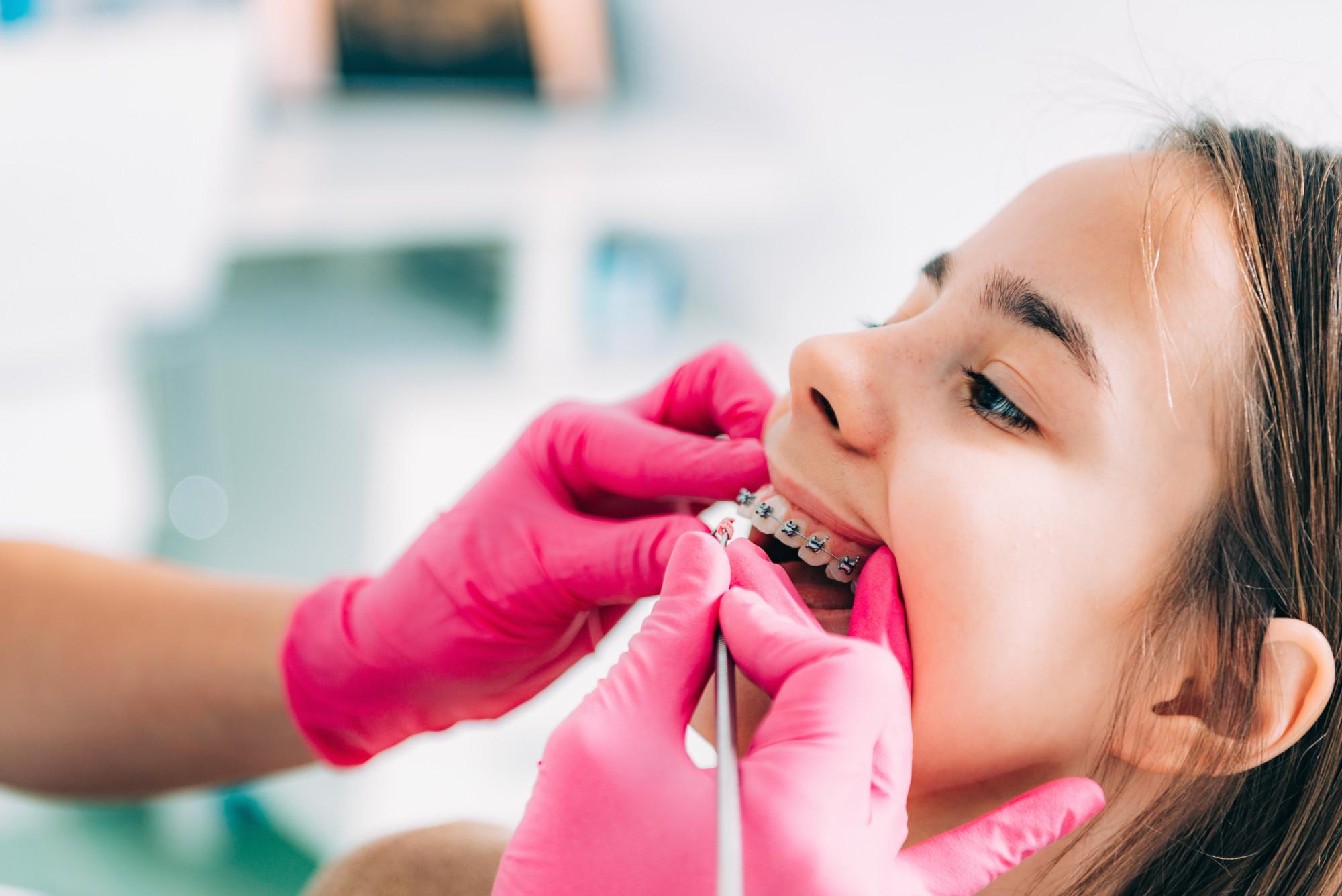 Orthodontist checking girl's dental braces